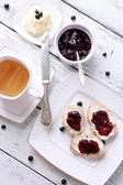 Fresh toasts with homemade butter and blackcurrant jam on wooden background — Stock Photo