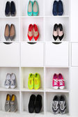 Colorful shoes on wooden shelves — Stock Photo