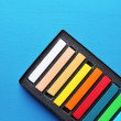 Colorful chalk pastels in box on color wooden background — Stock Photo #51288617