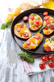 Tasty bruschetta with tomatoes on pan, on old wooden table — Foto Stock