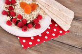 Big plate with oatmeal, small loaves of bread and berries on a polka dot napkin on wooden background — ストック写真