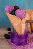 Tasty ice cream with berries in waffle cone on blue wooden background — Stock Photo