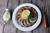 Round white plate of prawns with dill, lemon and sauce on a yellow napkin on grey wooden background — Stockfoto