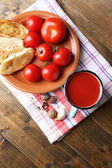 Homemade tomato juice in color mug, toasts and fresh tomatoes on wooden background — Stockfoto