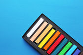 Colorful chalk pastels in box on color wooden background — Stock Photo