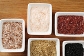 Variety of different sea salt in bowls on wooden table, close up — Stock Photo