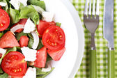 Salad with watermelon, onion, arugula and spinach leaves on plate, on wooden background — Stock Photo
