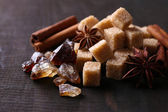 Brown sugar cubes and reed sugar, spices on wooden background — Stockfoto
