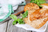 Fresh baked bread and fresh basil on cutting board, on wooden background — Stock Photo
