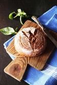 Vers gebakken brood en verse basilicum op snijplank, op houten achtergrond — Stockfoto