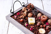 Candles on vintage tray with coffee grains and spices, bumps on color wooden background — Foto Stock