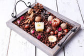 Candles on vintage tray with coffee grains and spices, bumps on color wooden background — 图库照片