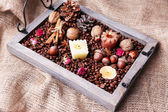 Candles on vintage tray with coffee grains and spices, bumps on sackcloth background — Foto Stock