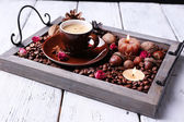 Candles on vintage tray with coffee grains and spices, cup of tea on color wooden background — Stock Photo