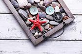 Velas en bandeja antigua con piedras de mar, conchas de mar y estrellas de mar sobre fondo de madera — Foto de Stock