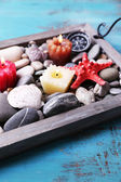 Candles on vintage tray with sea pebbles,starfish and sea shells on wooden background — Stock Photo