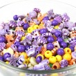 Multicoloured beads in glass bowl isolated on white — Stock Photo #51434383