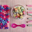 Multicoloured beads and lace stacked neatly on the table — Stock Photo #51434481