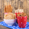 Dry breakfast, sticks and biscuits in red polka dot cup and plate on a napkin on wooden background — Stock Photo #51434811