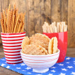Dry breakfast, sticks and biscuits in red polka dot cup and plate on a napkin on wooden background — Stock Photo #51434813