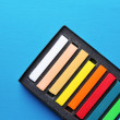 Colorful chalk pastels in box on color wooden background — Stock Photo #51435081