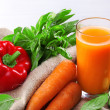 Glass of fresh carrot juice and vegetables on sacking napkin on wooden table — Stock Photo #51435159