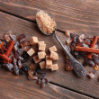 Brown sugar cubes, reed and crystal sugar, spices on wooden background — Stock Photo #51436153