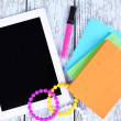 Tablet, bracelet, notebook and pen on wooden background — Stock Photo #51436309