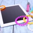 Tablet, bracelet, notebook and pen on wooden background — Stock Photo #51436317