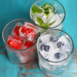 Ice cubes with mint leaves, raspberry and blueberry in glasses, on color wooden background — Stock Photo #51439157