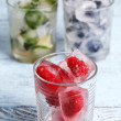 Ice cubes with mint leaves, raspberry and blueberry in glasses, on color wooden background — Stock Photo #51439177