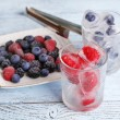 Frozen berries and ice cubes with mint leaves, raspberry and blueberry in glasses, on color wooden background — Stock Photo #51439183