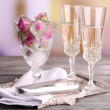 Ice cubes with rose flowers in glass bowl and two glasses with champagne on wooden table, on bright background — Stock Photo #51439617