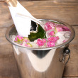 Frozen rose flowers in ice cubes and champagne bottle in bucket, on wooden background — Stock Photo #51439667