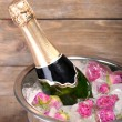 Frozen rose flowers in ice cubes and champagne bottle in bucket, on wooden background — Stock Photo #51439669