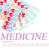 Prescription drugs on money background, representing rising health care costs, isolated on white — Stockfoto