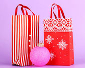Christmas paper bags for gifts on purple background — Stock Photo