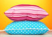 Blue bright pillows on orange background — Stock Photo