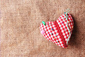 Fabric heart with color pins on sackcloth background — Stock Photo