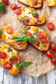 Tasty bruschetta with tomatoes , on old wooden table — Stock Photo