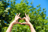 Young girl holding hands in heart shape framing on nature background — Stock Photo
