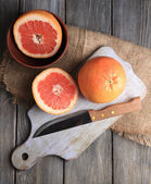 Ripe grapefruits and knife on cutting board, on wooden background — Stock Photo