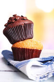 Tasty muffins on napkin, on bright background — Stock Photo
