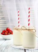 Milk in bottles with paper straws on table — Stock Photo