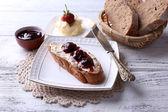 Verse toast met zelfgemaakte boter en strawberry jam op lichte houten achtergrond — Stockfoto