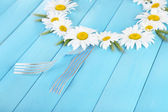Chamomile wreath on blue wooden background — Stock Photo