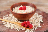 Big brown bowl with oatmeal and berries on a wooden table — Foto de Stock