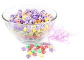 Multicoloured beads in glass bowl isolated on white — Stock Photo