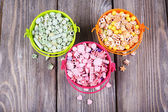 Beads in metal buckets on wooden background — Stock Photo