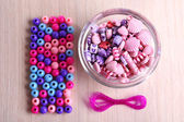Multicoloured beads and lace stacked neatly on the table — Stock Photo